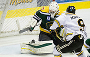 Powell River Kings goaltender Brian Wilson makes a pad save as Victoria Grizzlies forward Keyvan Mokhtari looks for a rebound at the Q Centre in Colwood, British Columbia Canada on March 27, 2017.