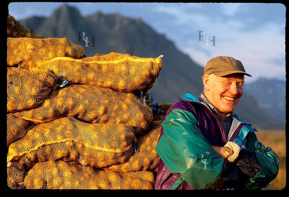 Farmer relaxes against sacks of newly-harvested potatoes on a September eve; Snaefellsnes, Iceland.