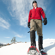 young man snowshoeing in mountains