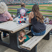 Lexi Russell, 4, of Craigsville, gazes at a phone while her family watches the West Virginia Power-Lakewood baseball game at Appalachian Power Park in Charleston, W.Va., on April 17, 2019.