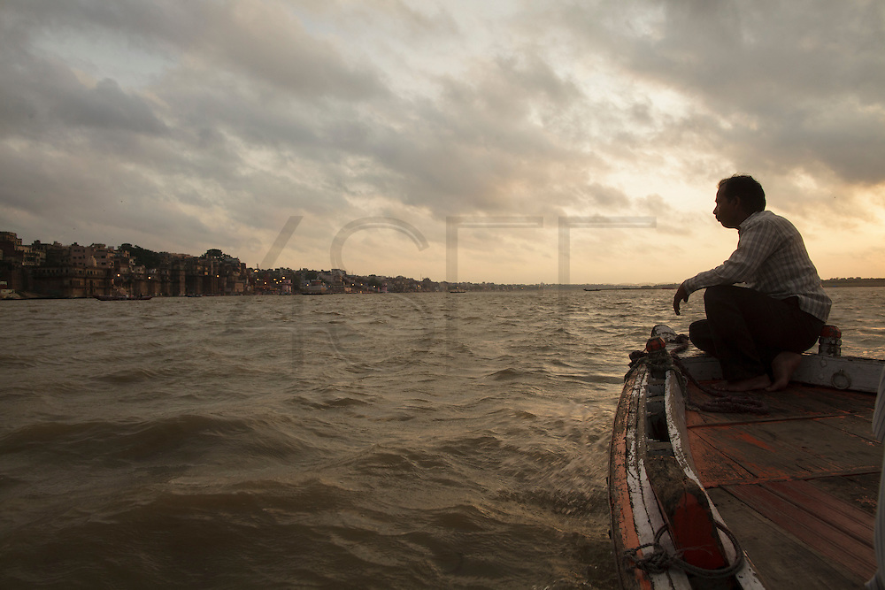 Sillouetted boatman at dawn navigating on Ganges river, in Varanasi, in India.
