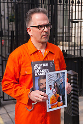 London, March 17th 2015.  Marathon-running Birmingham doctor David Nicholl, dressed in orange overalls delivers a petition to Downing Street clalling for the release of Shaker Aamer, a former UK resident who has been held at Guantánamo Bay without charge or trial for over 13 years.