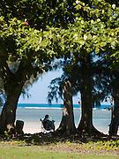 Man sitting and reading by Anini Beach on Kaua'i, Hawai'i