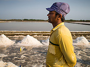 09 MARCH 2015 - NA KHOK, SAMUT SAKHON, THAILAND: A Burmese migrant worker on a salt farm near Samut Sakhon, Thailand, during the salt harvest. The coastal provinces of Samut Sakhon and Samut Songkhram, about 60 miles from Bangkok, are the center of Thailand's sea salt industry. Salt farmers harvest salt from the waters of the Gulf of Siam by flooding fields and then letting them dry through evaporation, leaving a crust of salt behind. Salt is harvested through dry season, usually February to April. The 2014 salt harvest went well into May because the dry season lasted longer than normal. Last year's harvest resulted in a surplus of salt, driving prices down. Some warehouses are still storing salt from last year. It's been very dry so far this year and the 2015 harvest is running ahead of last year's bumper crop. One salt farmer said prices are down about 15 percent from last year.    PHOTO BY JACK KURTZ