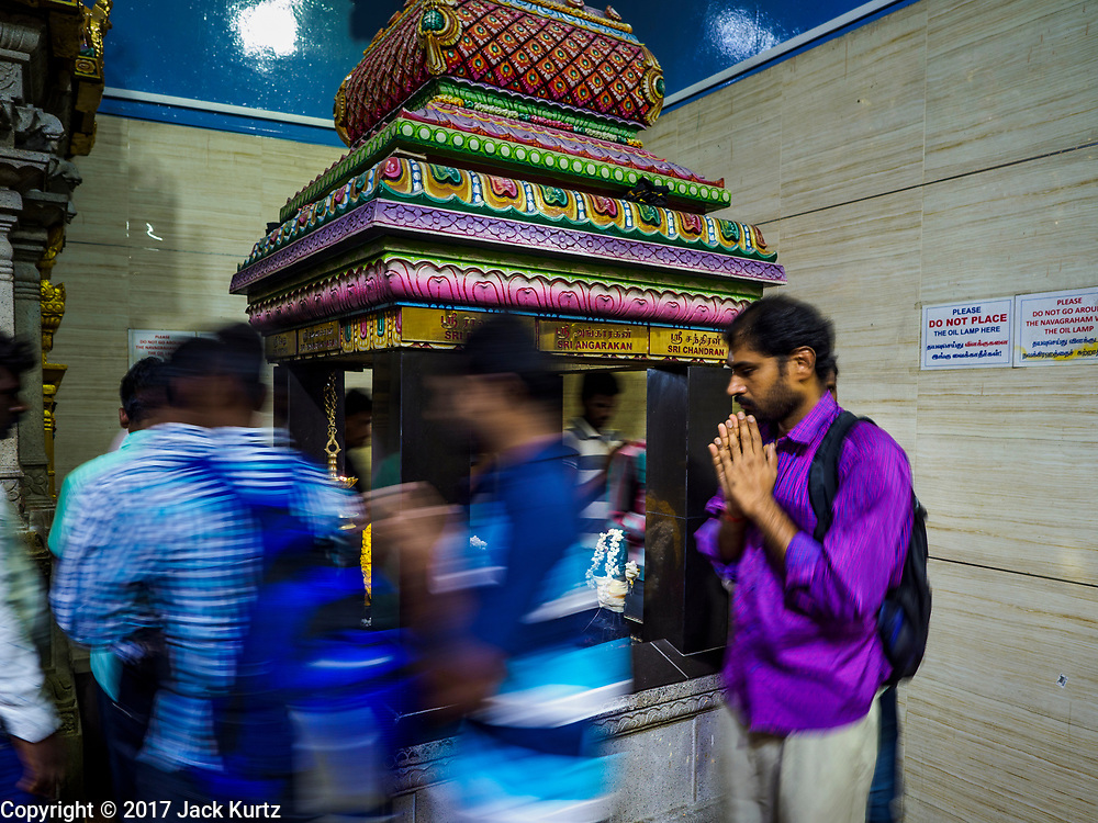 """09 JULY 2017 - SINGAPORE: Hindu guest workers in Singapore walk around a deity in Sri Veeramakaliamman Temple in Singapore's """"Little India."""" There are hundreds of thousands of guest workers from the Indian sub-continent in Singapore. Most work 5 ½ to six days per week. On Sundays, the normal day off, they come into Singapore's """"Little India"""" neighborhood to eat, drink, send money home, go to doctors and dentists and socialize. Most of the workers live in dormitory style housing far from central Singapore and Sunday is the only day they have away from their job sites. Most work in blue collar fields, like construction or as laborers.    PHOTO BY JACK KURTZ"""