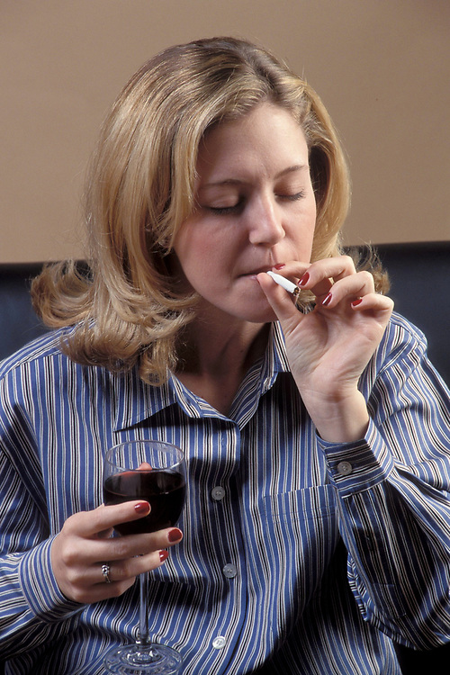 Young Anglo professional woman relaxes with a glass of wine and a Marijuana joint at home after work.  Model Release.<br /> ©Bob Daemmrich