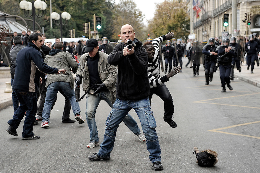 A plain-clothes policeman targeting the crowd during a student demonstration on on Darcy Square, while his colleagues are trying to arrest one of them. Dijon, France - October 15th 2010.