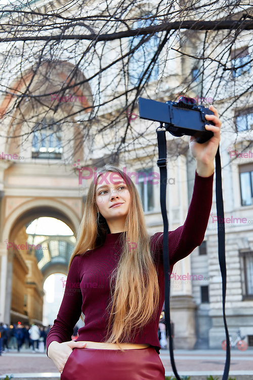 Girl takes a selfie with a camera outside of Galleria VIttorio Emanluele II Milano Italo Europe Vertical
