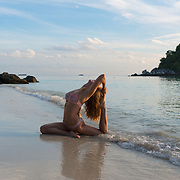 Beach yoga girl in pigeon pose on Thailand empty beach, Ko Lipe