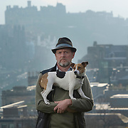 Writer Alex Renton with his dog Ziggy on Calton Hill, Edinburgh. To the right is the Dugald Stewart Monument. Picture Robert Perry 26th March 2014