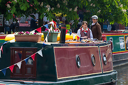 Little Venice, London, April 30th 2017. Narrowboaters from all over the uK gather for the annual Canalway Cavalcade, held on the May Day Bank holiday weekend, organised by the Inland Waterways Association, where boaters get the chance to display their immaculately prepared and brightly painted craft as well as compete in various manoeuvring tests. PICTURED: A pair of women make their way towards the start of a manoeuvring test.<br /> Credit: ©Paul Davey<br /> To licence contact: <br /> Mobile: +44 (0) 7966 016 296<br /> Email: paul@pauldaveycreative.co.uk<br /> Twitter: @pauldaveycreate