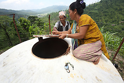 Kumari Sarki checks the water levels in the holding tank close to the water source that provides drinking water to the village gravity flow taps at a NEWAH WASH water project in Puware Shikhar, Udayapur District, Nepal.