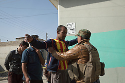 Licensed to London News Pictures. 11/11/2016. Mosul, Iraq. A soldier, of the Iraqi Army's 9th Armoured Division, searches a man in Mosul's Al Intisar district as residents queue to receive food from local volunteers. The Al Intisar district was taken four days ago by Iraqi Security Forces (ISF) and, despite its proximity to ongoing fighting between ISF and ISIS militants, many residents still live in the settlement without regular power and water and with dwindling food supplies.<br /> <br /> The battle to retake Mosul, which fell June 2014, started on the 16th of October 2016 with Iraqi Security Forces eventually reaching the city on the 1st of November. Since then elements of the Iraq Army and Police have succeeded in pushing into the city and retaking several neighbourhoods allowing civilians living there to be evacuated - though many more remain trapped within Mosul.  Photo credit: Matt Cetti-Roberts/LNP