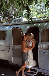 couple kissing by an airstream
