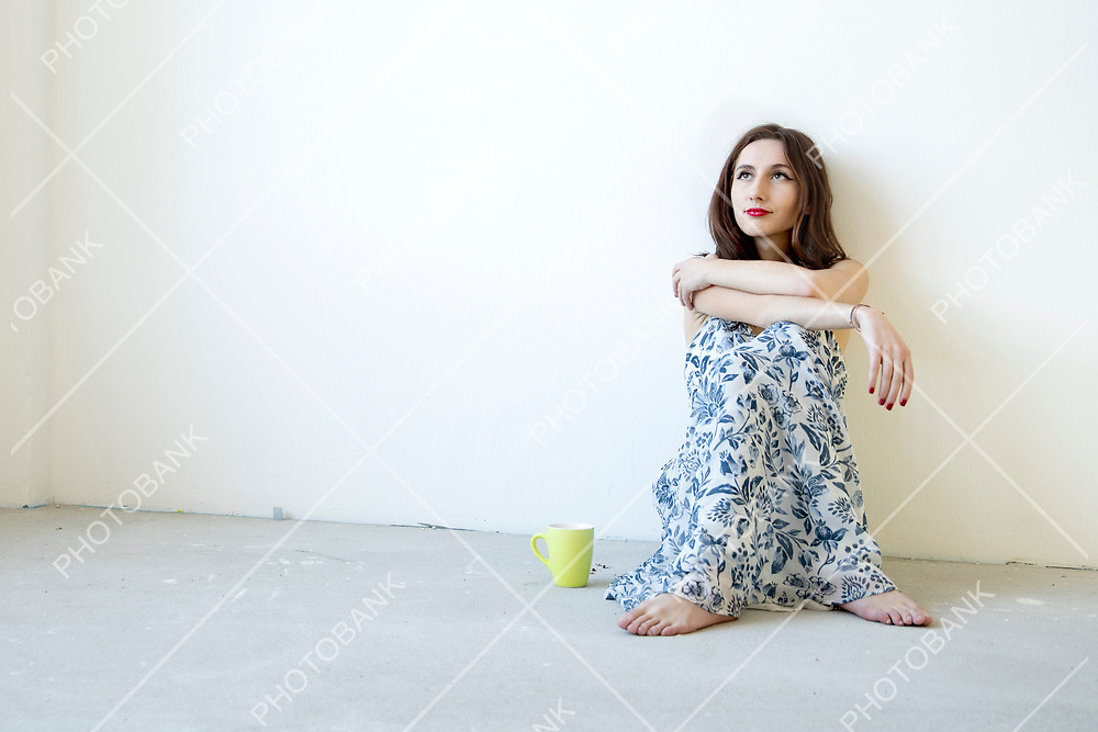 girl sitting on the ground with a yellow cup while thinking about her professional future