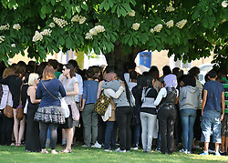© licensed to London News Pictures. LONDON UK. 25/04/11. School  friends gather under a tree.  Friends and family gather at a memorial service in a park in Chiswick, London, today (25 April 2011) to remember Isobel Reilly who died after a party in the early hours of Saturday morning. Photo credit should read Stephen Simpson/LNP