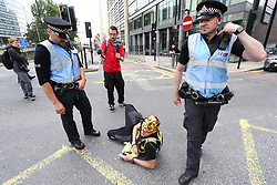© Licensed to London News Pictures. 24/07/2021. Manchester, UK. An Anti-lockdown protesters lies in the road during a protest in central Manchester. Protests have been organised in over 200 cities as part of a 'World Wide Rally for Freedom', calling for an end to lockdowns, the wearing of face masks and mandated vaccinations. Photo credit: Adam Vaughan/LNP