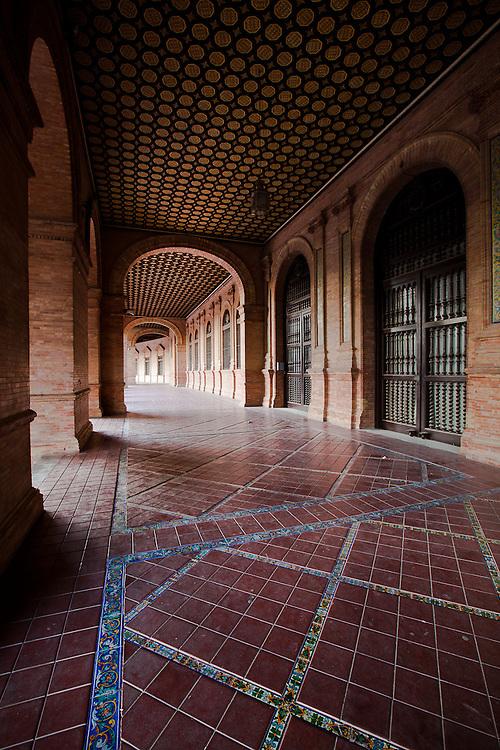 An image of geometry- a long corridor in the Plaza de Espana. Seville, Spain