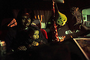 """Yardani and his son, with Perri, listen to music in his camping car. Manouche camping site, at night,  on the outskirts of Saintes Maries de la Mer<br /><br />""""Le Pelerinage des Gitans""""; the French gypsy pilgrimage of Saintes Maries de la Mer, Camargue, France<br /><br />Sainte Sara is an uncannonized saint, who legend says looked after the Christian Saints Marie Jacobe and Marie Salome, cousins of Mary Magdalene, who arrived, it is said, on the shores of the Camargue in a rudderless boat. Saint Sara is the patron saint of gypsies who come from far and wide to see her. There are even paintings of Sara as 'Kali' the black saint in Eastern Europe. Sara may have been the priestess of 'Ra' the sun-god or even servant girl to the Christian saints. No-one really knows.<br /><br />For a few weeks of the year, Roma, Gitan and Manouche gypsies come from all over Europe in May, camping in caravans around Saintes Maries de la Mer. It is a festive time where they play music, dance, party and christen their children. They all go to see Saint Sara in the crypt, kissing or touching her forehead. Many put robes on her shoulders, making her fat for the procession. In the main Gypsy procession of the 24th May, Saint Sara is allowed to leave her crypt, beneath the church, and is carried from the church to the shores of the mediterranean and back again. One day a year she is free from her prison. Hundred's of years ago the Gypsies used not even to be allowed into the church, only into the crypt like Sara...<br /><br />Roma gypsies still suffer oppressive prejudice and racism and are one of the ethnic groups the most persecuted and marginalised across Europe. The festival is one of the times where they celebrate with people of all races, their faith and traditions"""