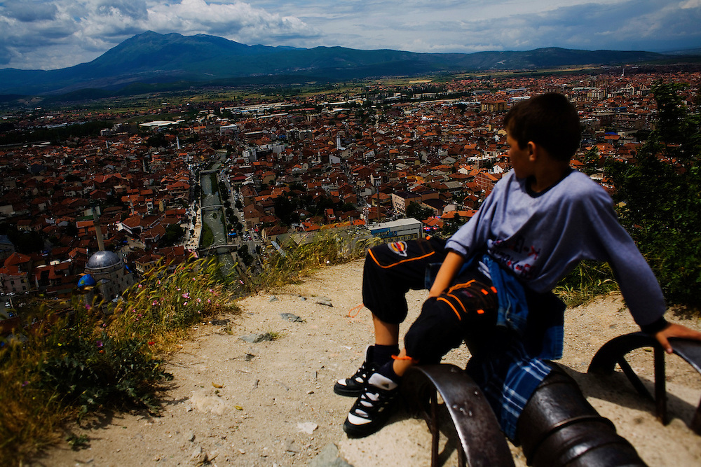 A boy sits on a commemorative cannon at the old fortress overlooking the city of Prizren in southwestern Kosovo.