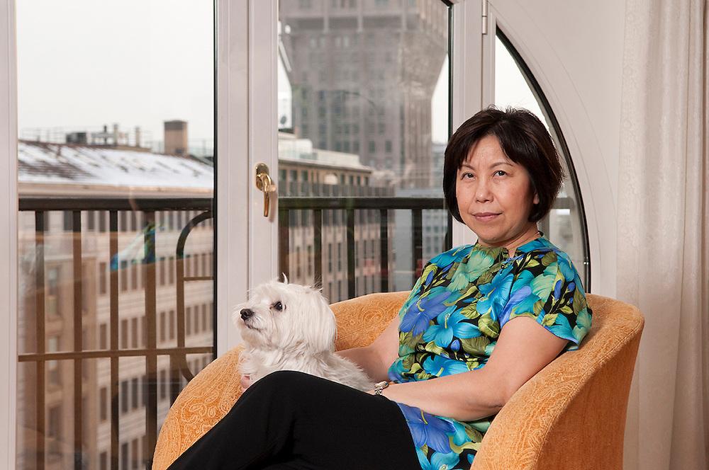 Chinese lady wiht her dog in her apartment in Milan. Carmen Sun is owner of Giardino di Giada