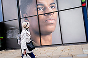 A woman of colour walks beneath the large billboard, a portrait of English football player, Marcus Rashford, outsidee the Strand branch of Coutts Bank, on 14th October, 2021, in Westminster, London, England. Marcus Rashford has recently been awarded an honourary degree by The University of Manchester in recognition of his political campaigning on behalf of the underprivilged (in particular, of school meals) and his philanthropy. He currently plays for Manchester United and is in the English national team. He has also been the victim of online racial abuse.