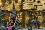 Tourists taking photo, Wat Phra Kaew - Temple of the Emerald Buddha - in the Dusit area of Bangkok.