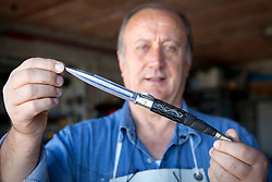 """Avigliano (PZ), 04-10-2010 ITALY - Vito Aquila, artigiano di Balestre. Il coltello di Avigliano, comunemente conosciuto come """"balestra"""", impreziosito con decorazioni in argento e ottone che le conferivano un certo valore non solo artistico,ha identificato per tutto l'Ottocento e parte del Novecento il carattere fiero e risoluto del popolo aviglianese, come attestato in una lunga casistica di riscontri documentari. La """"balestra"""" è un'arma a tutti gli effetti, ed è già considerata -nell'ambito delle manifatture di ferro - oggetto di pregio. Per l'approvvigionamento dell'argento e dell'ottone destinati alla decorazione del manico del coltello gli armieri si rivolgevano agli orefici o agli ottonari. La """"balestra"""" era un'arma del popolo, pronta ad essere impiegata, a seconda delle circostanze, per la difesa o l'offesa tanto dagli uomini quanto dalle donne. Queste, la ricevevano come regalo di fidanzamento dal rispettivo promesso sposo per meglio difendere il proprio onore, perpetrando un'usanza molto sentita almeno fino ai primi decenni del '900..Nella Foto: Vito Aquila mostra la balestra finita."""