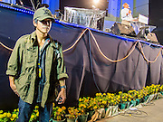 03 JANUARY 2014 - BANGKOK, THAILAND: A bodyguard stands next to the stage while SUTHEP THAUGSUBAN speaks to anti-government protestors in Bangkok at Democracy Monument. Thousands of Thai anti-government protestors came to Democracy Monument in Bangkok Friday night to hear Suthep outline his plans to shut down the city of Bangkok. Suthep said his protestors would occupy 20 major intersections in the commercial sections of Bangkok for up to three weeks or until the caretaker government of Yingluck Shinawatra resigns.     PHOTO BY JACK KURTZ