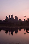 Pink sky dawn sunrise at Angkor Wat. This jewel in the crown of Angkor's ancient temples is a vision of beauty, might and Khmer architectural excellence. The five towers dominate the view, which you are led to trough outer walls, along causeways over the moat and past the two giant pools which act as a mirror of the vision. Consecrated at around 1150 to the Hindu god, Vishnu it is suggested that construction took 30 years.