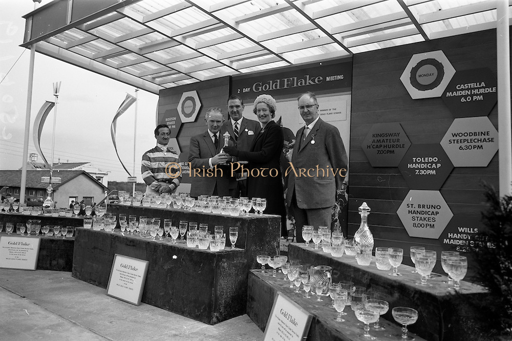 """08/05/1965<br /> 05/08/1965<br /> 08 May 1965<br /> The 1965 Gold Flake Meeting at Leopardstown Racecourse, Co. Dublin. Image shows Mrs D.R. Mott, wife of the Managing Director of Wills of Dublin and Cork, presenting the Trophy  for the Wills Gold Flake Stakes to Mr M.V. (Vincent) O'Brien, Trainer, who accepted it on behalf of the Countess de la Valdeme, who's """"Donato"""" won the race. Also in the picture are (from left) Jack M. Purtell (Jockey) Mr. D.R. Mott and Mr Fred Clarke, Managing Director of Leopardstown Club. Note the Waterford Glass Crystal Service sets presented to the winning owner, trainer and jockey."""