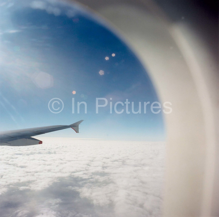 From an airliner passenger seat, bright sunshine causes lens flare during a flight across the English Channel between Paris and London. We see out at a cruising altitide across the clouds that blanket the ground below. The curve of the Airbus window makes for a corner along the right-hand side of the image.