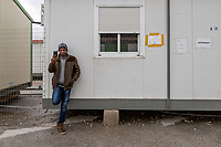 ATHENS, GREECE - FEBRUARY 05: A refugee stands while he speaks on the phone inside the Eleonas refugee camp on February 05, 2015 in Athens, Greece. Hundreds of refugees are transferred every day to Eleonas refugee camp while waiting to travel to the Macedonian border. Photo: © Omar Havana. All Rights Are Reserved