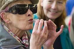 Visually impaired people with carers on outing to Denby Pottery. Woman with volunteer. Kissing clay frog - prince?