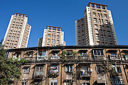 Old traditional tenement housing in shadow of new modern high rise apartment blocks at Mahalaxmi in Mumbai, India