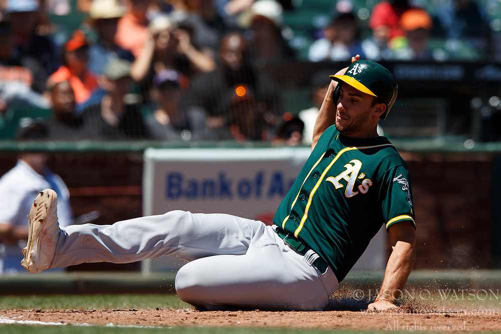 SAN FRANCISCO, CA - JULY 15: Stephen Piscotty #25 of the Oakland Athletics slides into home plate to score a run against the San Francisco Giants during the fourth inning at AT&T Park on July 15, 2018 in San Francisco, California. The Oakland Athletics defeated the San Francisco Giants 6-2. (Photo by Jason O. Watson/Getty Images) *** Local Caption *** Stephen Piscotty