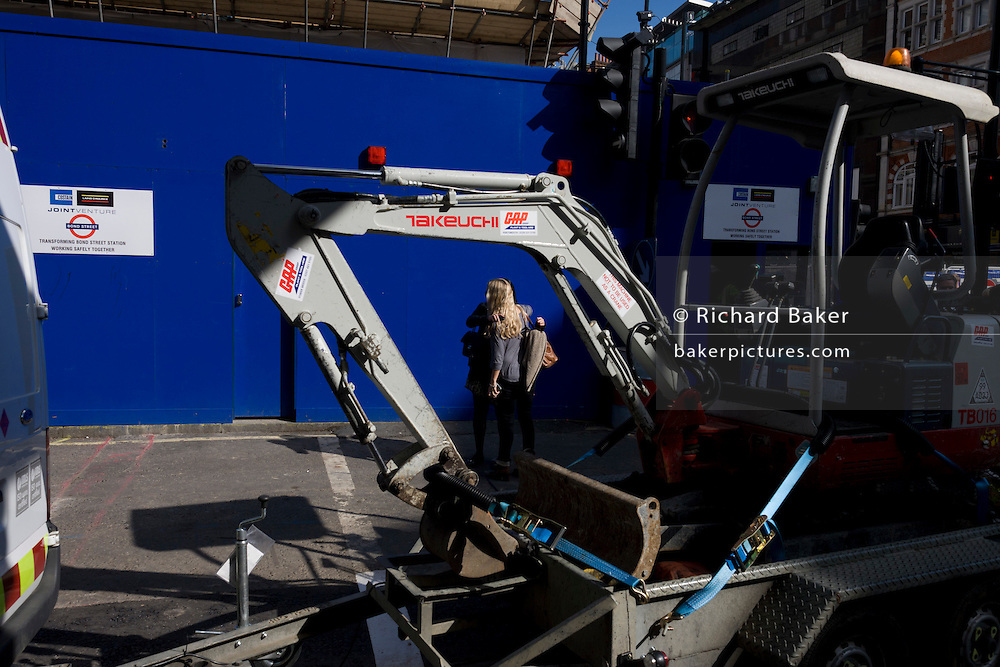 Seen through the folded arm of a small excavator, two friends hug against the blue hoarding of Bond Street works.