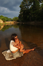 Menes Perez, left, and her husband Renato look after  their daughter Delisa Perez while their son Alberto, 3, swims by.  The Chavez government is attempting to erradicate illiteracy in Venezuela through a program known as Plan Robinson.  In their effort to spread the classes to every corner of the country they have arrived to communities like Limon de Parhuena, situated on the edge of the Venezuelan-Colombian border.