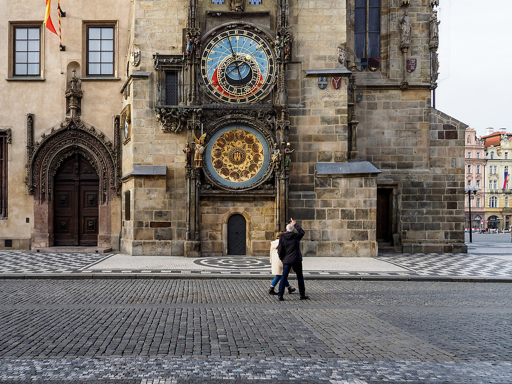 A couple passing the Astronomical clock at Old Town Square in Prague. As of 21st of October 2020 people have to wear face masks outside and inside.