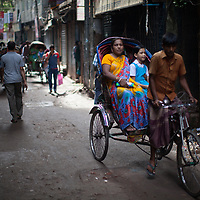 A rickshaw driver with clients makes his way along a street in old Dhaka, Bangladesh.