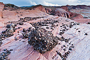 Conglomerate rock erodes on top of ancient sandstone in the White Domes area of Valley of Fire State Park, Nevada, USA. Dedicated in 1935, it is the oldest state park in Nevada. Starting more than 150 million years ago, great shifting sand dunes during the age of dinosaurs were compressed, uplifting, faulted, and eroded to form the park's fiery red sandstone formations. The park adjoins Lake Mead National Recreation Area at the Virgin River confluence, at an elevation of 2000 to 2600 feet (610-790 m), 50 miles (80 km) northeast of Las Vegas, USA. Park entry from Interstate 15 passes through the Moapa Indian Reservation.