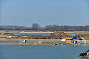 Nederland, Nijmegen, 12-3-2015 Aan de overkant van de Waal bij Lent wordt druk gewerkt aan het creeren van een nevengeul in de rivier om bij hoogwater een betere waterafvoer te hebben. Werkzaamheden aan de drempel met de doorlaatgaten.Het is een omvangrijk project waarbij onder meer de pijlers van het spoorviaduct een bredere basis moeten krijgen omdat die straks in de loop van het water staan. Ook de n325 die vanaf de Waalbrug naar Arnhem loopt moet over 400 meter opnieuw worden aangelegd omdat het talud vervangen wordt door pijlers. De weg wordt via een bypass omgeleid. Het dorp veurlent komt op een kunstmatig eiland te liggen met twee bruggen als ontsluiting. Een voetgangersbrug en de andere voor normaal verkeer. Inmiddels begint de nieuwe kade aan de noordkant van deze geul vorm te krijgen. Ruimte voor de rivier, water, waal. In de nieuwe dijk wordt een drempel gebouwd die stapsgewijs water doorlaat en bij hoogwater overloopt. Measures taken by Nijmegen to give the river Waal, Rhine, more space to flow during highwater and to prevent the risk of flooding. Room for the river. Reducing the level, waterlevel. Foto: Flip Franssen/Hollandse Hoogte