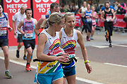 A female runner encourages a teammate during the finale 600 metres of The Virgin London Marathon at Birdcage Walk on 28th April 2019 in London in the United Kingdom. Now in it's 39th year, the London Marathon is a large sporting event with over 40,000 runners expected to take part.