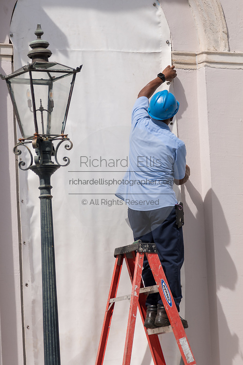 Workers attach hurricane cloth to windows on the Charleston City Hall in preparation for approaching Hurricane Florence September 11, 2018 in Charleston, South Carolina. Florence, a category 4 storm, is expected to hit the coast between South and North Carolina and could be the strongest storm on record for the East Coast of the United States.