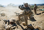 A Marine fires a grenade launcher above fellow Marines as they lay down suppressive fire during live-fire exercises at Camp Pendleton.