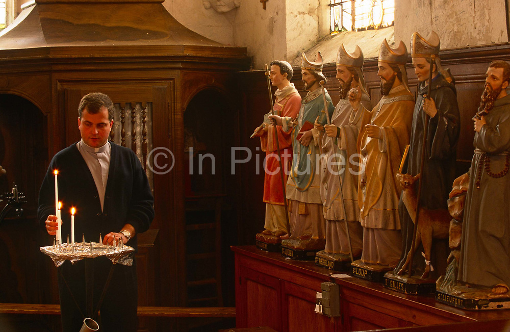 Watched by statues of saints, Father Phillipe Dubos a country priest lights candles before Sunday Mass in a local Catholic church in Iville St Guerisseurs, rural Normandy. In front of the statues of six saint icons that are lined up along a raised surface in the transept, a quiet corner of the church. It is estimated that somewhere between 83% to 88% of France's population are Catholic. The church is organised into 98 dioceses, served by 20,523 priests.