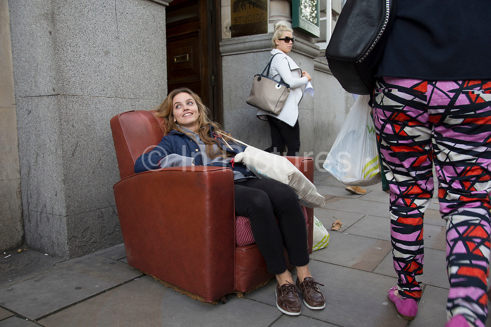 Woman takes the weight off her feet to relax in an armchair which has been abandoned on the street in Earls Court, London, UK. Laughing at the weirdness of the street scene as people pass by.