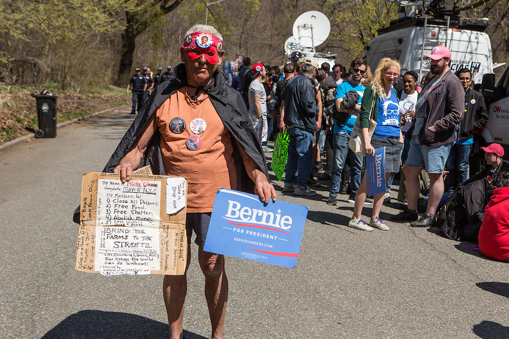 """Brooklyn, NY - 17 April 2016. A man who identified himself as Ricky Obama carries a Bernie sign alog with his poplitical manifesto. Vermont Senator Bernie Sanders, who is running as a Democrat in the U.S. Presidential primary elections, held a campaign """"get out the  vote"""" rally in Brooklyn's Prospect Park."""