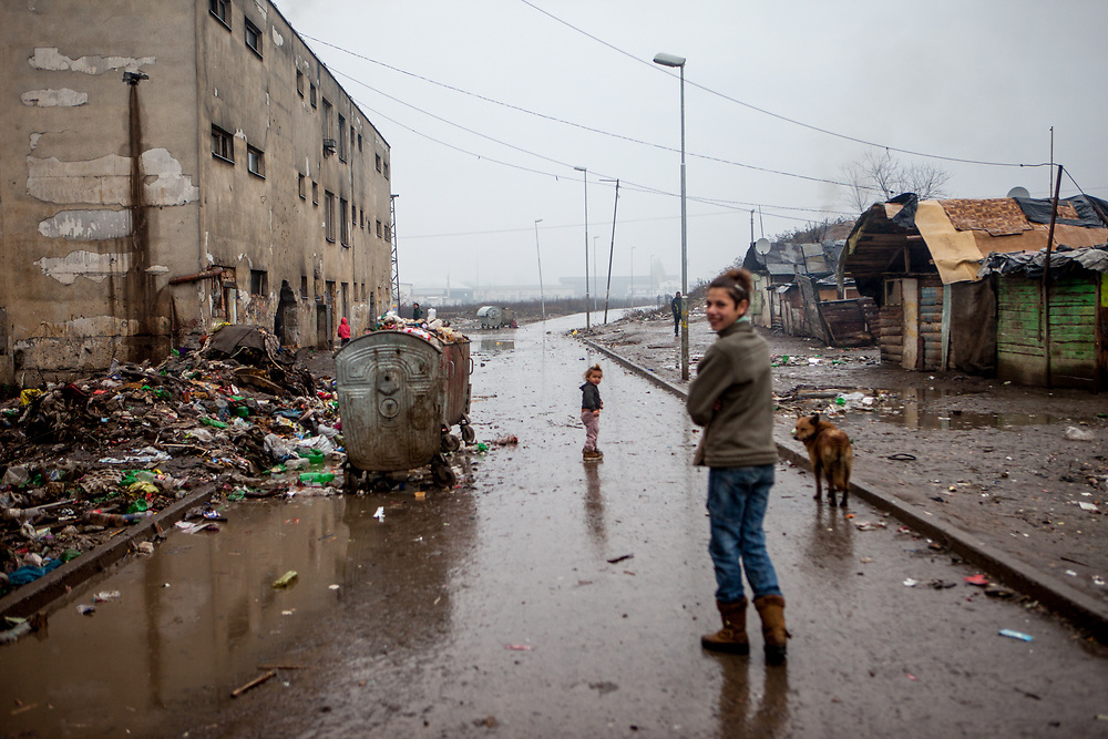 "The main road at the segregated Roma settlement ""Budulovska Street"" (2016). In 2015 the ""muddy"" roads to and in the settlement were asphalted and the infrastructure for the residents  improved. The city has roughly 11200 inhabitants, about 1980 (18%) of them have Roma ethnicity and around 800 are living at the segregated settlement 'Budulovska Street' (2014)."