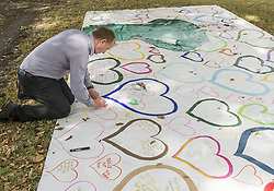 March 16, 2019 - Christchurch, Canterbury, New Zealand - People write messages of hope on a large plastic tarp across the street from the Al Noor mosque, where 41 people were killed. (Credit Image: © PJ Heller/ZUMA Wire)